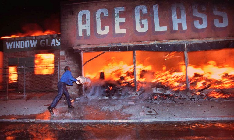 Cornelius Pettus, owner of Payless market, throws a bucket of water on the flames at neighboring business Ace Glass during the first night of the Los Angeles Riots in Los Angeles, California in this April 29, 1992, file photo. This year marks the 20th anniversary of the L.A. Riots. REUTERS/Hyungwon Kang/Los Angeles Times/Files (UNITED STATES - Tags: CRIME LAW ANNIVERSARY SOCIETY CIVIL UNREST) NO SALES. NO ARCHIVES. FOR EDITORIAL USE ONLY. NOT FOR SALE FOR MARKETING OR ADVERTISING CAMPAIGNS. THIS IMAGE HAS BEEN SUPPLIED BY A THIRD PARTY. IT IS DISTRIBUTED, EXACTLY AS RECEIVED BY REUTERS, AS A SERVICE TO CLIENTS. MANDATORY CREDIT ORG XMIT: HWK103